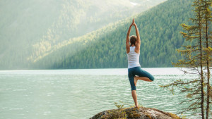 22482185 - young woman is practicing yoga at mountain lake